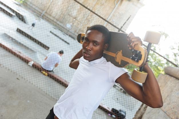 Schwarzer junge mit longboard am park