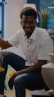 Schwarzer junger erwachsener, der in kunstwerk-studio-zeichnungsvase mit bleistift und weißer leinwand auf staffelei sitzt. afroamerikanischer mann mit kreativer beschäftigung, der innovative meisterwerke und bildende kunst macht