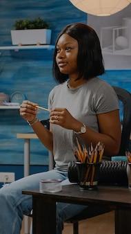 Schwarzer junger künstler, der zu hause an vasenzeichnung arbeitet