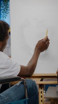Schwarzer junger künstler mit behinderung, der vasendesign auf leinwand erstellt, während er zu hause im atelierraum sitzt. afroamerikaner mit behinderung im rollstuhl zeichnen meisterwerk