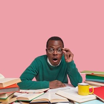 Schwarzer junger männlicher lehrer sieht verblüfft aus, überrascht über den vortrag von morgen, hält die hand am brillenrand