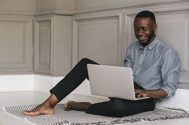Schwarzer junger mann, der mit einem laptop auf dem boden sitzt und arbeitet. hochwertiges foto