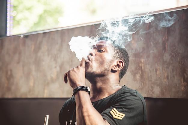 Schwarzer junger mann, der raucht und mit dem rauch von einer wasserpfeife spielt