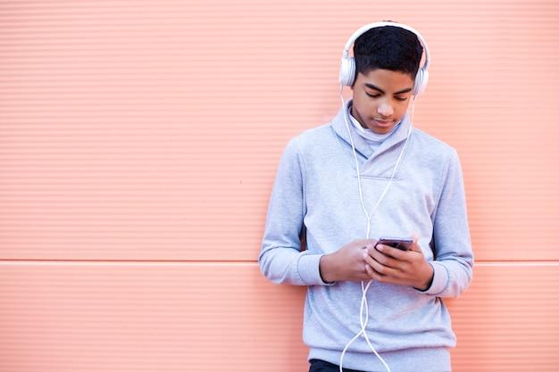 Schwarzer junger mann hört musik an seinem handy bei der stellung auf der straße. afroamerikanerjugendlicher in den kopfhörern unter verwendung eines smartphone.
