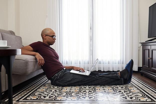 Schwarzer junger mann in gläsern, die auf dem boden in seinem zimmer sitzen und dokument auf laptop-bildschirm lesen