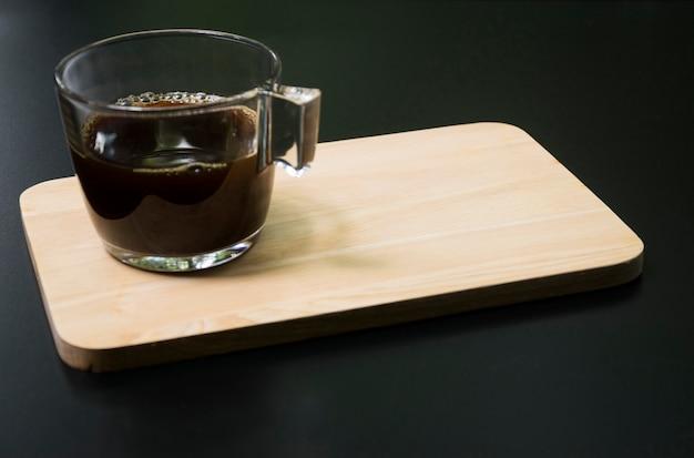 Schwarzer kaffee auf holzbrett morgenzeit
