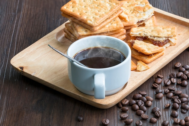 Schwarzer kaffee, cracker und kaffeebohne auf holz.