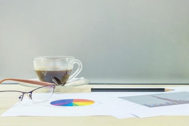 Schwarzer kaffee der nahaufnahme mit arbeitspapier auf hölzernem schreibtisch