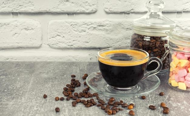 Schwarzer kaffee-espresso in einem glas mit sahne und marshmallows in einem glas. kaffeebohnen auf grauer und weißer backsteinmaueroberfläche mit kopierraum