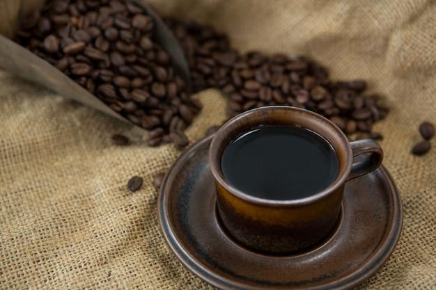Schwarzer kaffee, geröstete bohnen und schaufel auf sack