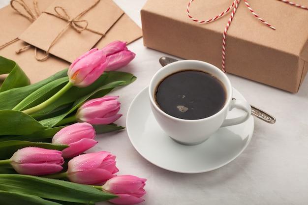Schwarzer kaffee im weißen cup und in den tulpen.