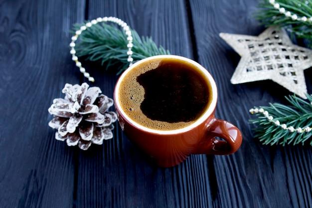 Schwarzer kaffee in der braunen keramikschale mit weihnachtszusammensetzung