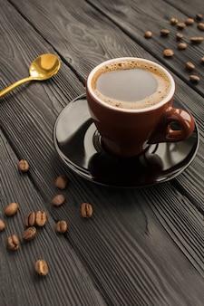 Schwarzer kaffee in der braunen tasse auf dem schwarzen