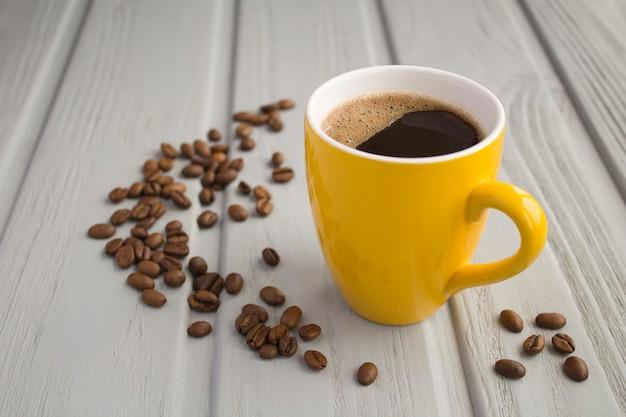 Schwarzer kaffee in der gelben tasse auf dem grauen hölzernen hintergrund