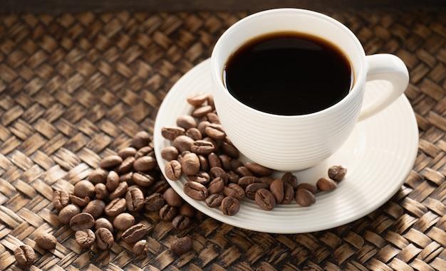 Schwarzer kaffee in der tasse, espresso und bohnen auf dem teller, koffein hilft, energie zu haben
