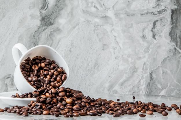 Schwarzer kaffee in der tasse und kaffeebohnen auf marmor
