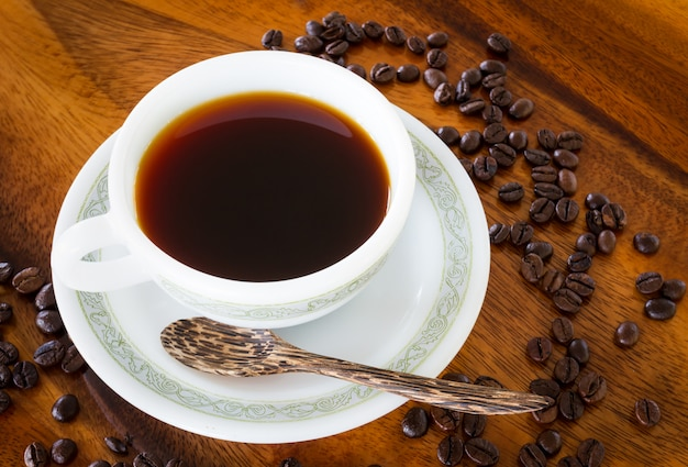 Schwarzer kaffee in der weißen kaffeetasse auf weinleseholztischhintergrund