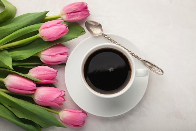 Schwarzer kaffee in der weißen schale und in den tulpen.
