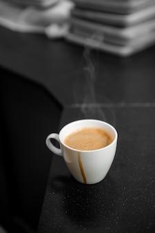 Schwarzer kaffee in der weißen tasse stellte auf kaffeetische