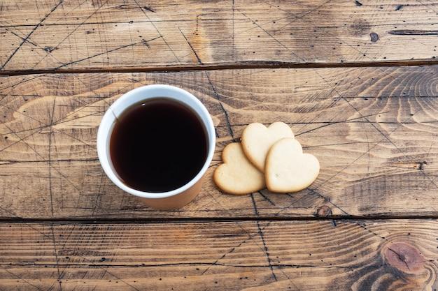 Schwarzer kaffee in einer pappbecher und kekse in der form von herzen auf einem hölzernen hintergrund. flach liegender kopierraum, draufsicht.