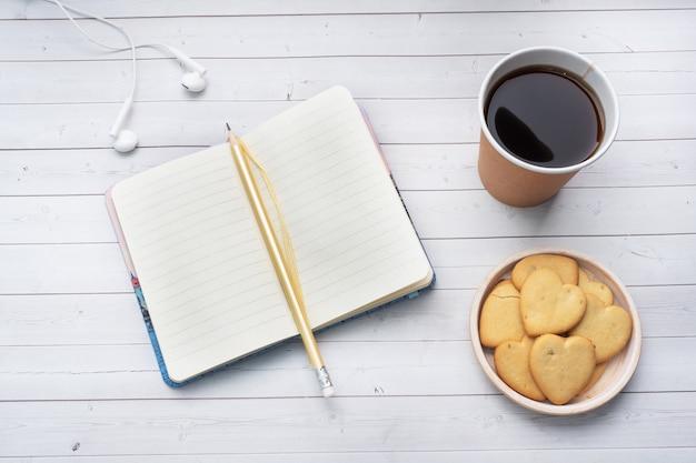 Schwarzer kaffee in einer pappbecher und kekse in der form von herzen auf einem weißen hintergrund. flach liegender kopierraum, draufsicht.