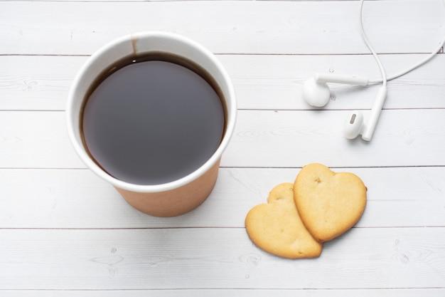 Schwarzer kaffee in einer pappbecher und kekse in form von herzen