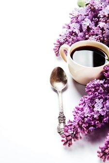 Schwarzer kaffee in einer tasse, zucker auf einem löffel und frische lila blumen