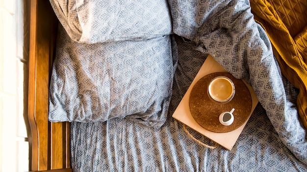 Schwarzer kaffee in einer transparenten schale im bett am herbstmorgen