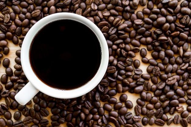 Schwarzer kaffee in einer weißen kaffeetasse mit kaffeebohnehintergrund
