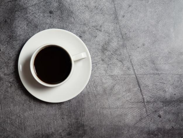 Schwarzer kaffee in einer weißen tasse auf einem konkreten hintergrund, den raum kopierend