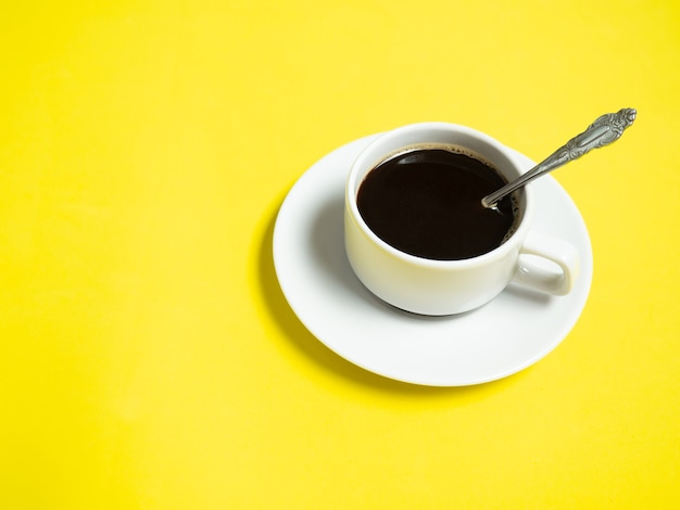 Schwarzer kaffee in einer weißen tasse auf gelbem hintergrund, kopierraum