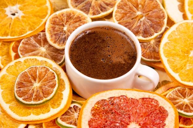 Schwarzer kaffee in einer weißen tasse, umgeben von getrockneten zitrusfrüchten