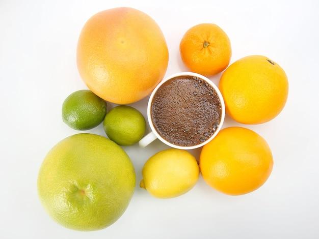 Schwarzer kaffee in einer weißen tasse, umgeben von zitrusfrüchten