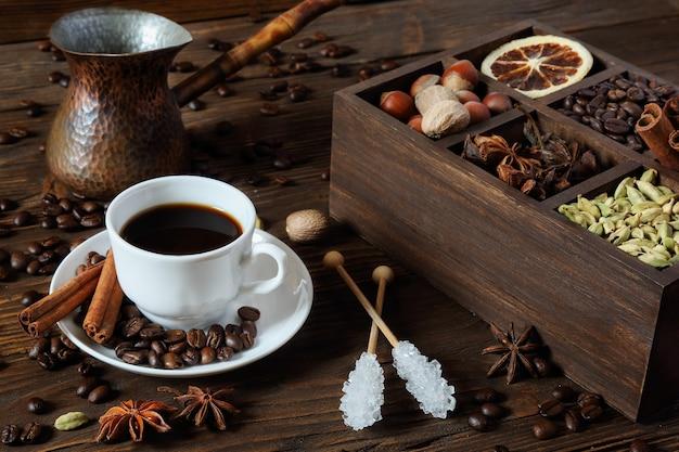 Schwarzer kaffee in einer weißen tasse, zucker und verschiedenen gewürzen auf einem holztisch