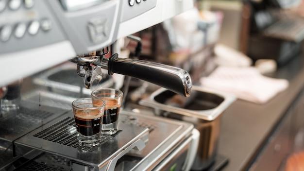 Schwarzer kaffee in messbecher auf kaffeemaschine setzen