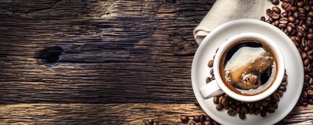 Schwarzer kaffee in porzellantasse mit verstreuten bohnen auf rustikalem holztisch. panoramabanner von oben.