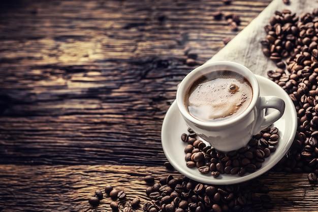 Schwarzer kaffee in porzellantasse mit verstreuten bohnen auf rustikalem holztisch.