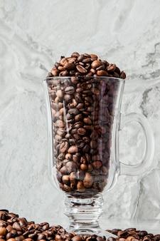 Schwarzer kaffee in tasse und kaffeebohnen auf marmorhintergrund. draufsicht, platz für text