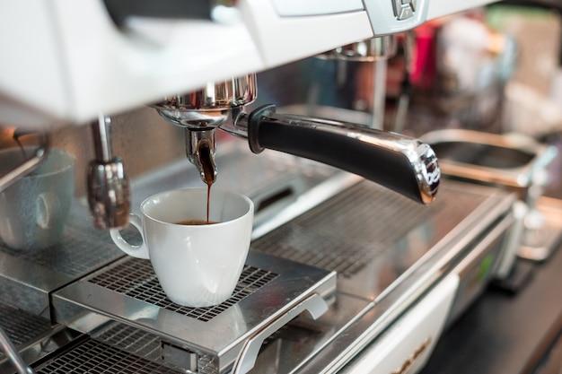 Schwarzer kaffee in weißer tasse auf kaffeemaschine setzen