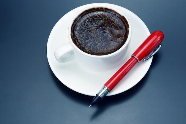 Schwarzer kaffee in weißer tasse und ein roter stift auf der untertasse