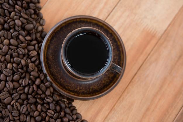 Schwarzer kaffee mit gerösteten kaffeebohnen