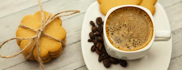 Schwarzer kaffee mit milchschaum auf einem hölzernen hintergrund, ingwerplätzchen und guter laune morgens