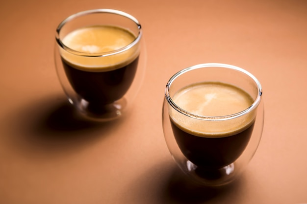 Schwarzer kaffee mit schaum in den modernen schalen auf ebene