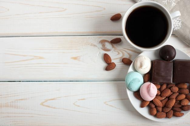 Schwarzer kaffee mit süßigkeiten und mandeln.