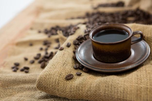 Schwarzer kaffee serviert auf sack mit kaffeebohnen