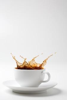 Schwarzer kaffee spritzt in weiße tasse