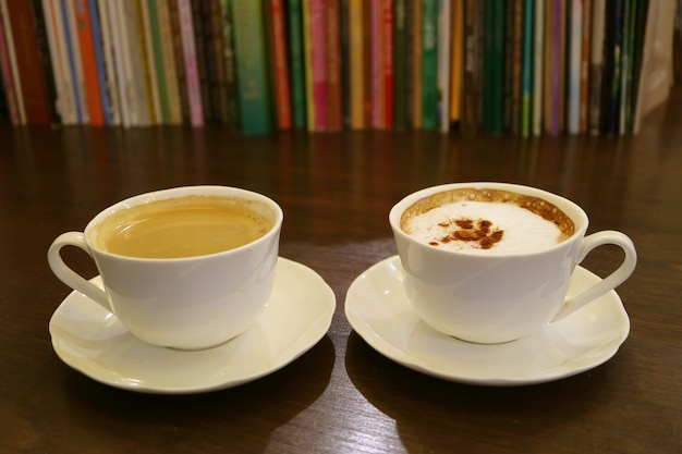 Schwarzer kaffee und cappuccino-kaffee mit verschwommenen reihen von büchern im hintergrund