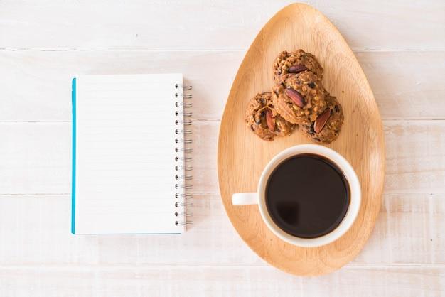 Schwarzer kaffee und kekse mit laptop und notizbuch