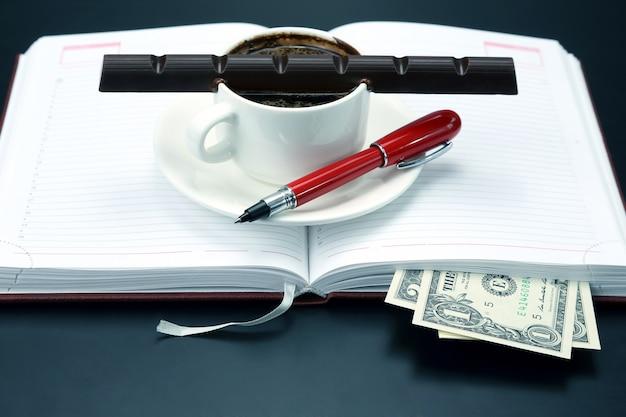 Schwarzer kaffee und schokolade auf dem tisch von einem geschäftsmann