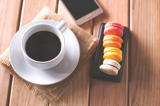 Schwarzer kaffee und süßigkeiten auf einen holzfußboden gelegt. zeit zum entspannen.